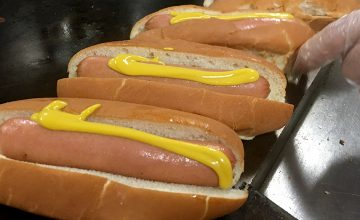 Made-to-order hot dogs are lined up in the kitchen ready to be served.
