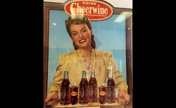 A vintage sign shows a woman serving Cheerwine in its classic glass bottles.
