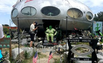 The Frisco UFO alien emerges from his ship. Owner Leroy Reynolds plays the role of alien, dressing in his old race car driving suit and lime green alien mask.
