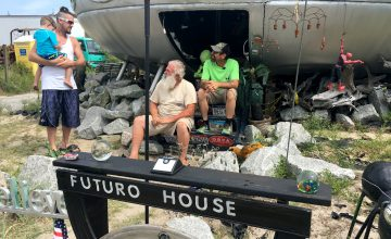 Property owner James Bagwell (left) and Futuro House owner Leroy Reynolds sit on the steps leading up to the Frisco UFO, greeting visitors.
