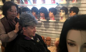 Trying on Gray Wig at Kim's — Kanupp helps customers try on wig after wig until they find one they love. Here she helps a man try on a gray wig while he looks in the mirror.