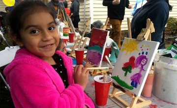 A girl shows her painting at a Red Calaca art truck event.