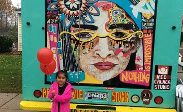 A girl poses in front of a Rosalía Torres-Weiner's mural on the Red Calaca art truck.
