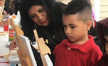 Rosalía Torres-Weiner helps a young artist with his painting.