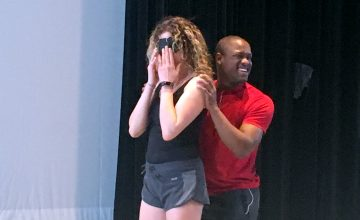 UNC-Charlotte student Davian Robinson leads one of his classmates through a blindfolded dance exercise, which helps his peers gain perspective into his daily life.