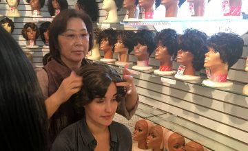 My Home, NC's Miriam McSpadden tries on a Wig — Kim's Wig Center owner Sandy Kanupp helps My Home, NC videographer Miriam McSpadden try on a wig.