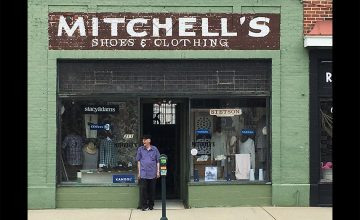 Owner of Mitchell's Clothing in Greensboro stands in front of the store, which has been open since 1939.