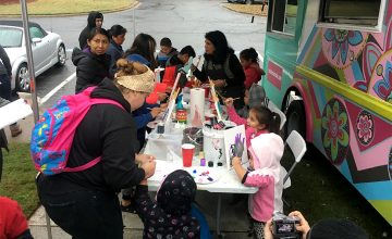 A group of children gathers to paint outdoors with Rosalía Torres-Weiner's art truck.