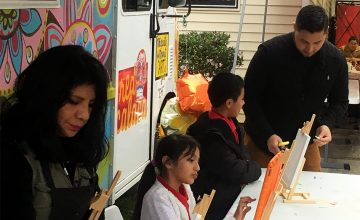 Rosalía Torres-Weiner helps children with their paintings.