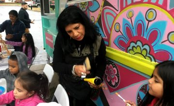 Rosalía Torres-Weiner brings out painting supplies to children from her art truck.