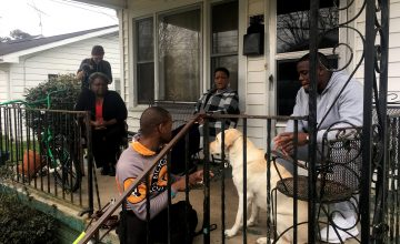 Davian Robinson and his family members congregate on the porch of his Hickory, NC home.